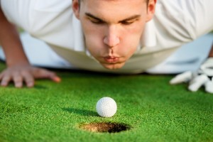 Golfer blowing on the golf ball