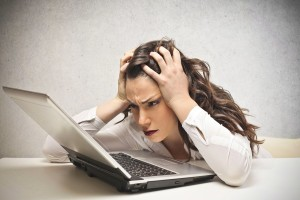 Stressed woman looks at a laptop